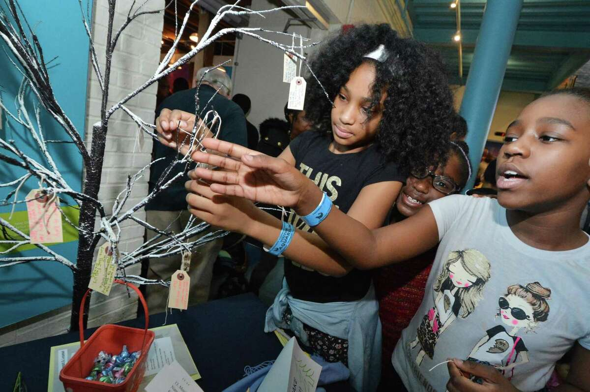 Malaiya Prosper and Joelle Roc place poems on a tree to help make a Poet-Tree with Norwalk poet laureate Laurel Peterson during 'South Norwalk Celebrating Diversity' sponsored by The Byrne Criminal Justice Innovation Program Team and co sponsored by Norwalk police and The Maritime Aquarium. A free