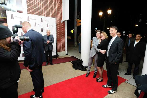 Dan Guller, center, hugs Janet James before they walk the red carpet at the Avon Theatre's 10th annual Avon Oscars Party in Stamford on Sunday.