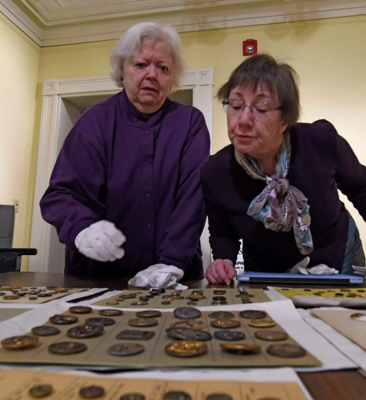 Volunteers June Kosier, left and Kathy Arbogast look over antique buttons for their quality of preservation and their intrinsic value at the Rensselaer County Historical Society Wednesday Feb. 22, 2017 in Troy, N.Y. (Skip Dickstein/Times Union)