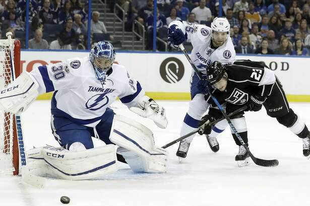 Tampa Bay Lightning goalie Ben Bishop (30) knocks the puck away as defenseman Braydon Coburn (55) and Los Angeles Kings right wing Dustin Brown (23) battle for position during the first period of an NHL hockey game Tuesday, Feb. 7, 2017, in Tampa, Fla. (AP Photo/Chris O'Meara)