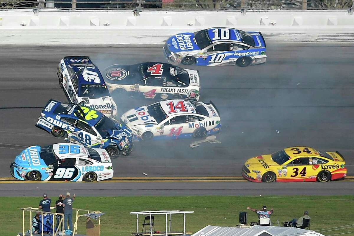 Jimmie Johnson (48), Clint Bowyer (14), Chris Buescher (37), Kevin Harvick (4), D.J. Kennington (96) and Danica Patrick (10) collide in a multi-car wreck between Turns 3 and 4, as Landon Cassill (34) drives past, during the NASCAR Daytona 500 auto race at Daytona International Speedway, Sunday, Feb. 26, 2017, in Daytona Beach, Fla. (AP Photo/Phelan M. Ebenhack) ORG XMIT: DBR310