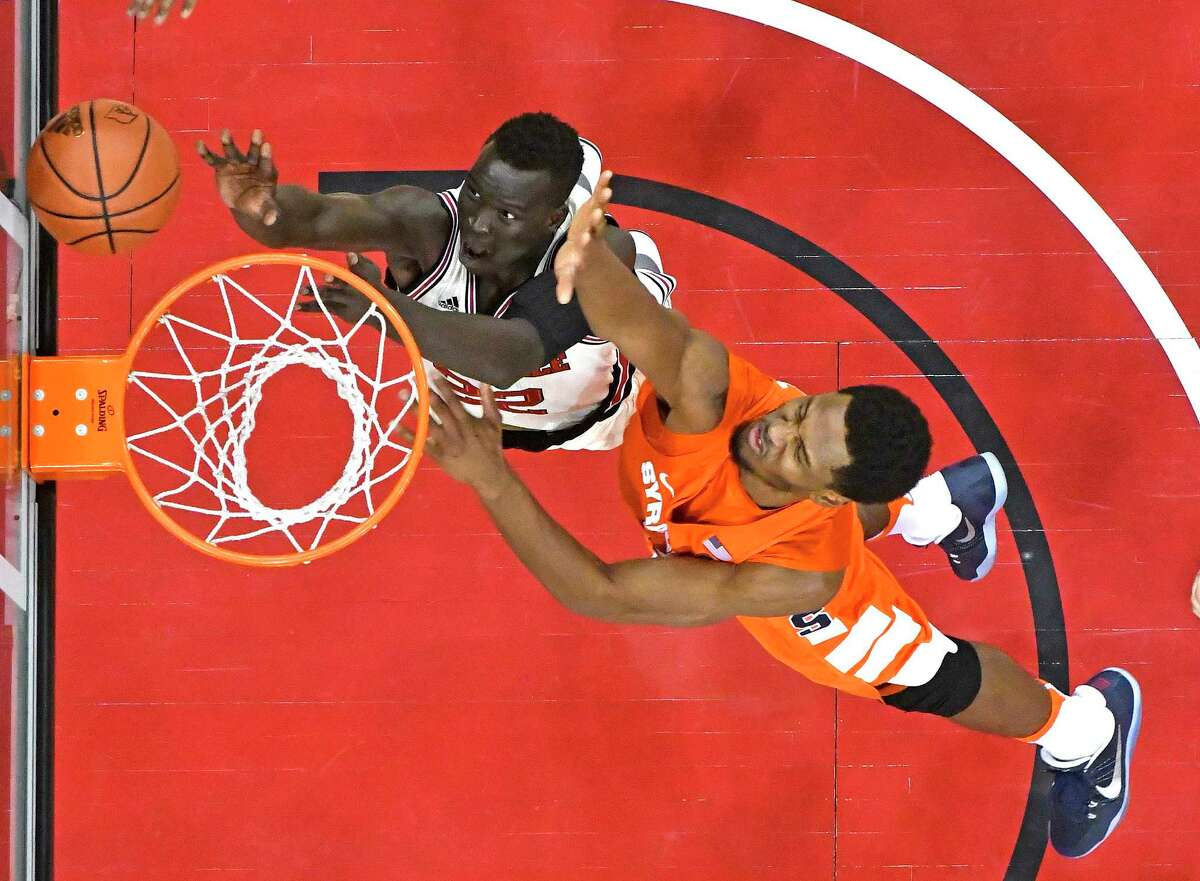 Louisville's Deng Adel (22) puts a shot up past the defense of Syracuse's Taurean Thompson (12) during the second half of an NCAA college basketball game, Sunday, Feb. 26, 2017, in Louisville, Ky. Louisville won 88-68. (AP Photo/Timothy D. Easley) ORG XMIT: KYTE116