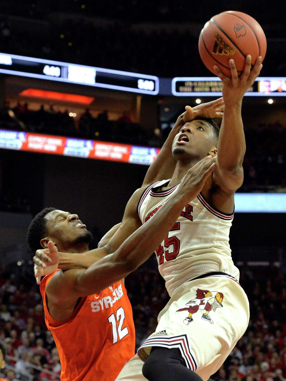 Louisville's Donovan Mitchell (45) is fouled by Syracuse's Taurean Thompson (12) during the second half of an NCAA college basketball game, Sunday, Feb. 26, 2017, in Louisville, Ky. (AP Photo/Timothy D. Easley) ORG XMIT: KYTE109
