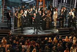 "The cast of ""Moonlight"" and """"La La Land"" appear on stage as presenter Warren Beatty (C), flanked by host Jimmy Kimmel (L) shows the winner's envelope for Best Movie ""Moonlight"" on stage at the 89th Oscars on February 26, 2017 in Hollywood, California."