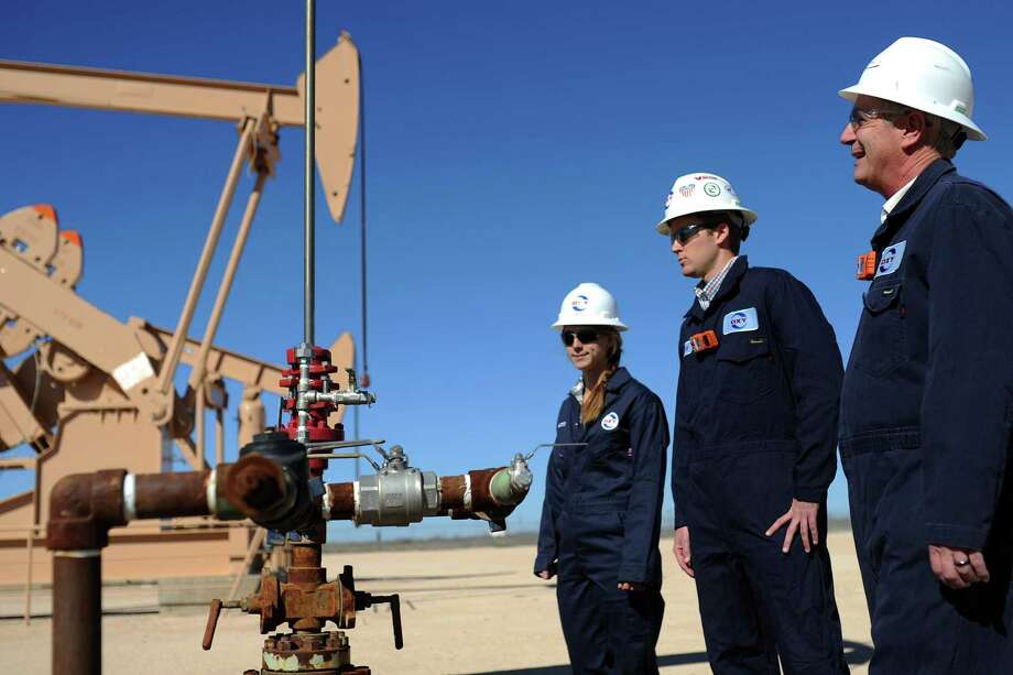 """Kent Dykstra (right), a training supervisor at Occidental, checks equipment engineers Jenny James (left) and Cody Carpenter this month. """"I feel like I have a lot of loyalty to Oxy for sending me out to the field,"""" James says. Photo: Photos By James Durbin /Midland Reporter-Telegram / © 2017 Midland Reporter Telegram. All Rights Reserved."""