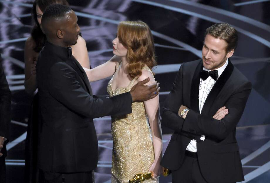 """Ryan Gosling, right, stands with his arms folded as Emma Stone, center, congratulates Mahershala Ali, for winning the award for best picture for """"Moonlight"""" at the Oscars on Sunday, Feb. 26, 2017, at the Dolby Theatre in Los Angeles. It was originally announced mistakenly that """"La La Land"""" was the winner. (Photo by Chris Pizzello/Invision/AP) Photo: Chris Pizzello, Associated Press"""