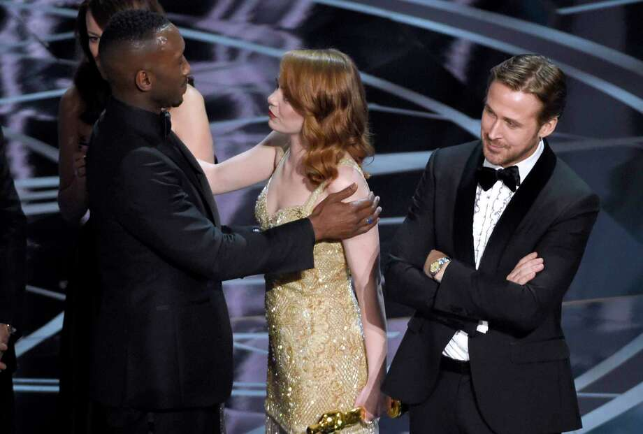 "Ryan Gosling, right, stands with his arms folded as Emma Stone, center, congratulates Mahershala Ali, for winning the award for best picture for ""Moonlight"" at the Oscars on Sunday, Feb. 26, 2017, at the Dolby Theatre in Los Angeles. It was originally announced mistakenly that ""La La Land"" was the winner. (Photo by Chris Pizzello/Invision/AP) Photo: Chris Pizzello, Chris Pizzello/Invision/AP / 2017 Invision"