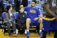 Zaza Pachulia plays with his son Saba's, 7, hair as Davit, 8, watches before the Golden State Warriors played the Los Angeles Clippers at Oracle Arena in Oakland, Calif., on Thursday, February 23, 2017.