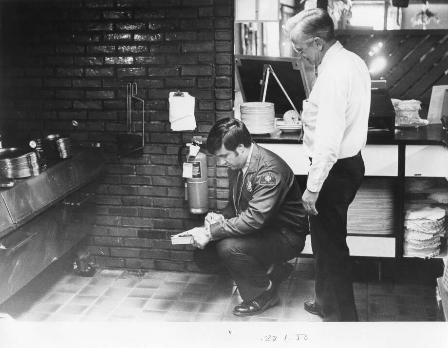Gene Chase, a firefighter inspects the fire extinguisher at Ponderosa Steak House as manager James Hoogerhyde stands nearby. October 1984 Photo: Daily News File Photo