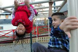 Ngameh, of Albany, originally from Thailand, 8, left, and Sehail Mohamad, of Albany, originally from Afghanistan, 7, play on monkey bars on Nov. 9, 2015 in Albany, N.Y. (Lori Van Buren / Times Union)