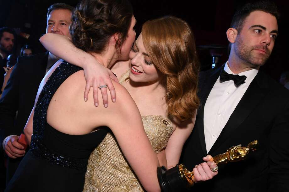 "Winner for Best Actress ""La La Land"" Emma Stone (R)  poses with a guest and her brother Spencer at the 89h Annual Academy Awards Governors Ball in Hollywood, California, on February 26, 2017. Photo: ANGELA WEISS/AFP/Getty Images"