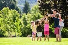 Teacher and young children play outdoors. Pre-K. Kindergarten. Spring. Summer.