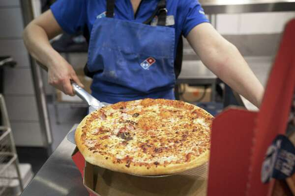 An employee places a cooked pizza into a delivery box inside a Domino's Pizza Group Plc store in Hanwell, London, U.K., on Monday, Feb. 27, 2017. Domino's Pizza said given continued strong new store performance and positive outlook both for its market and brand, it is increasing its long term target for the U.K. to 1,600 stores. Photographer: Jason Alden/Bloomberg