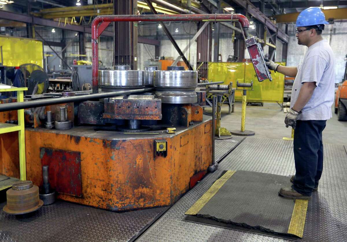 Alamo Iron Works' Javier Perez operates a bending machine in the company's 140,000 square foot metal storage and fabrication facility. In June, Texas manufacturers added 2,200 jobs statewide, according to a new report from ADP.