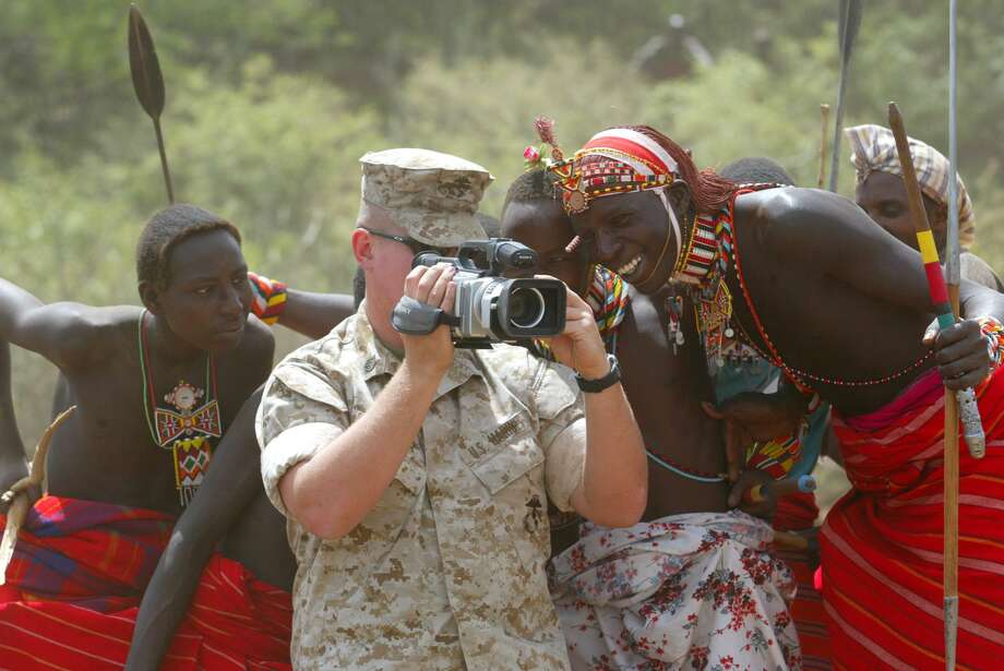 Samburu men watch Staff Sgt. Mathew Butler from the U.S Army's 412th Civil Affairs Battalion film cattle, Friday, June 11, 2004 in the village of Amaiya in north western Kenya. U.S. troops are working in Amaiya doing medical and veterinary work which is populated primarily by herdsman living of pastoral land. The US soldiers are based in Djibouti, a tiny Horn of Africa nation that since 2002 has been home to the headquarters of a U.S.-led task force leading the war on terrorism in eastern Africa.(AP Photo/Karel Prinsloo) Photo: KAREL PRINSLOO, STF / AP / AP