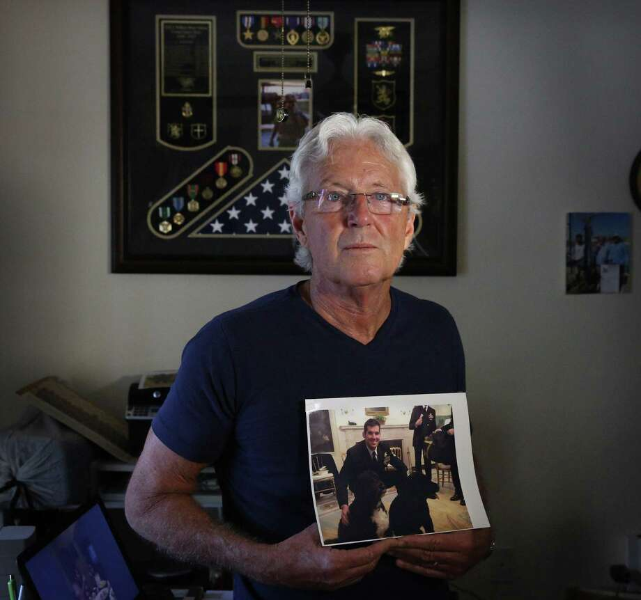 """In this February 2017 photo, William Owens holds a photo of his youngest son Navy SEAL William """"Ryan"""" Owens in Lauderdale by the Sea, Fla. Ryan Owens was killed during an anti-terrorism raid in Yemen. In the photo Ryan Owens was visiting the White House and posed for a photo with then President Barack Obama's dogs after being awarded medals for his service. (Emily Michot/Miami Herald via AP) Photo: Emily Michot, MBO / Associated Press / Miami Herald"""