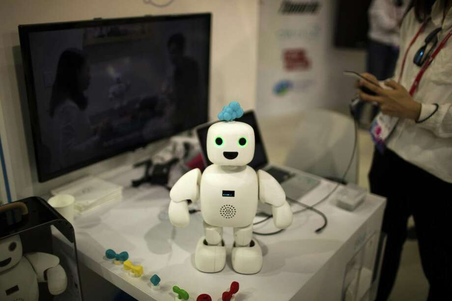 Pibo robot, whose main purpose is getting you and your loved ones sharing your daily life again, receives instructions from her owner Monday at the Mobile World Congress in Barcelona, Spain. Photo: Emilio Morenatti /Associated Press / Emilio Morenatti