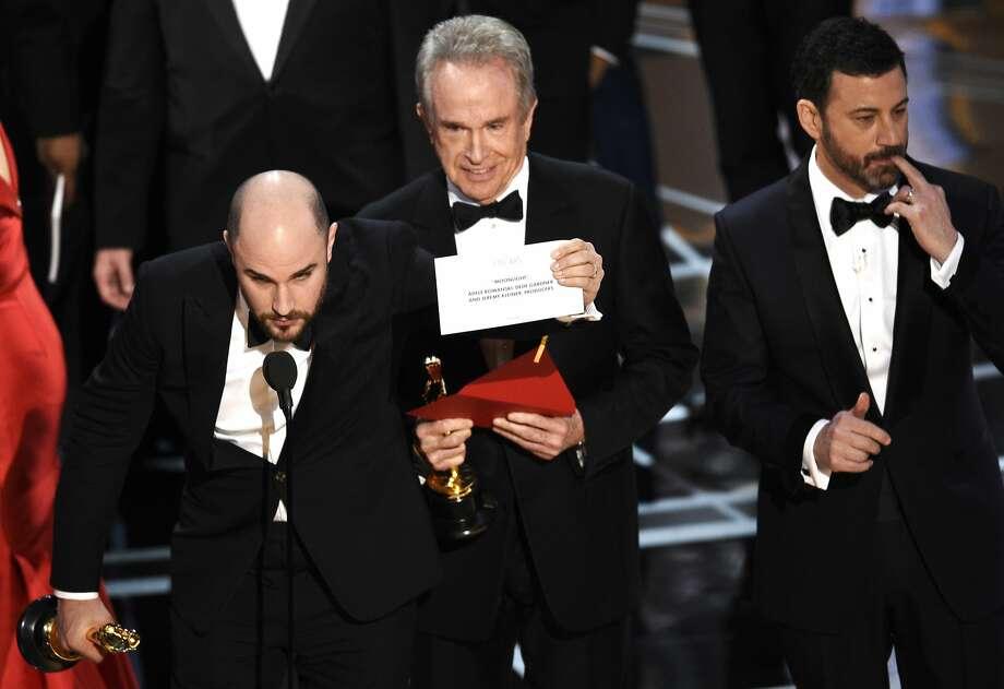 "Jordan Horowitz (left) shows the card revealing ""Moonlight"" as the true winner of best picture, alongside presenter Warren Beatty and Oscar host Jimmy Kimmel. Photo: Chris Pizzello, Associated Press"