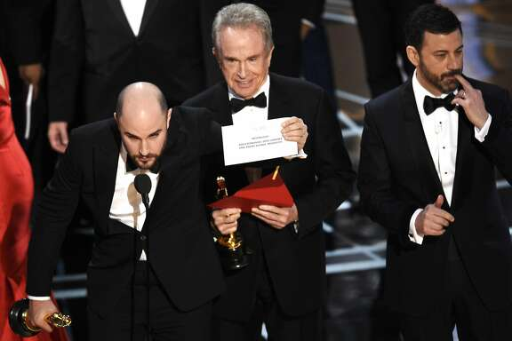 "Jordan Horowitz shows the envelope revealing ""Moonlight"" as the true winner of best picture at the Oscars on Sunday, Feb. 26, 2017, at the Dolby Theatre in Los Angeles. Host Jimmy Kimmel and presenter Warren Beatty look on from right. (Photo by Chris Pizzello/Invision/AP)"