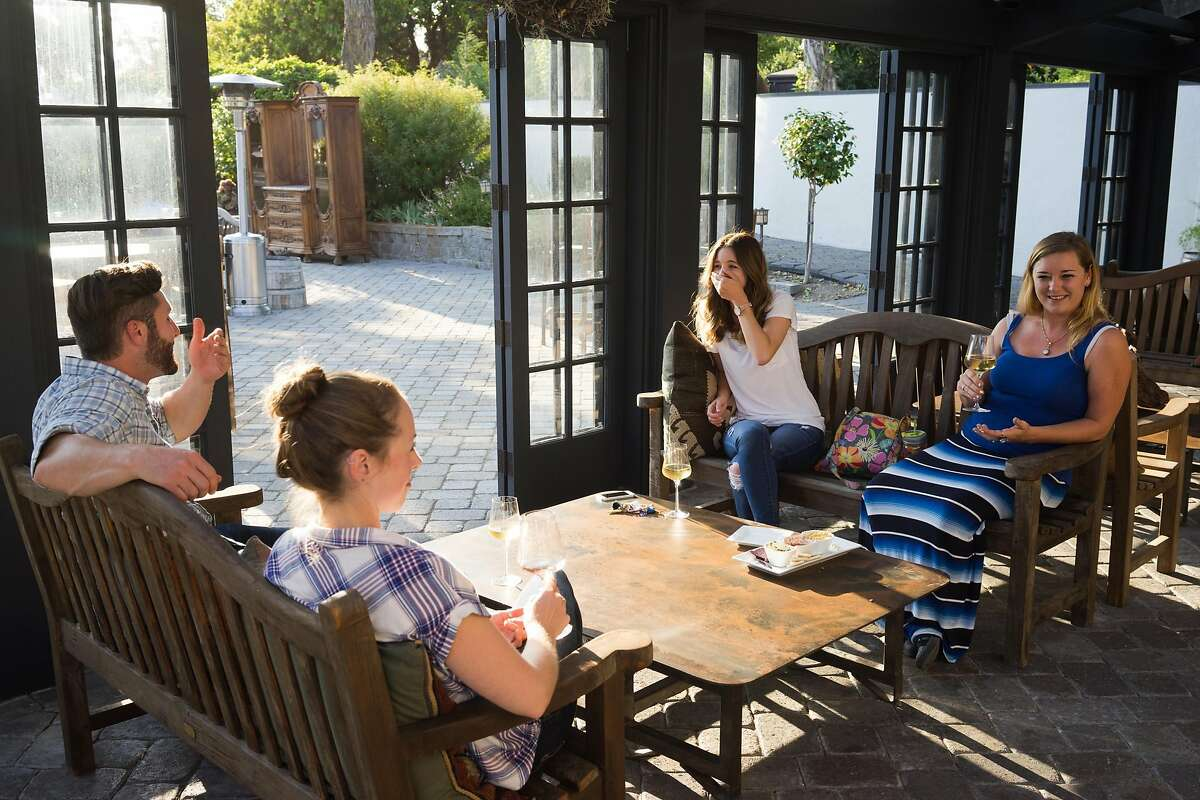 Left to right, Kyle Yedlicka, Kaylin Berkheimer, Kacy Wyman and Samantha Schroeder sample wine at Folktale Winery in Carmel, Calif. on Sunday, Aug. 30, 2015. The winery features a new outdoor pavilion for guests to enjoy.