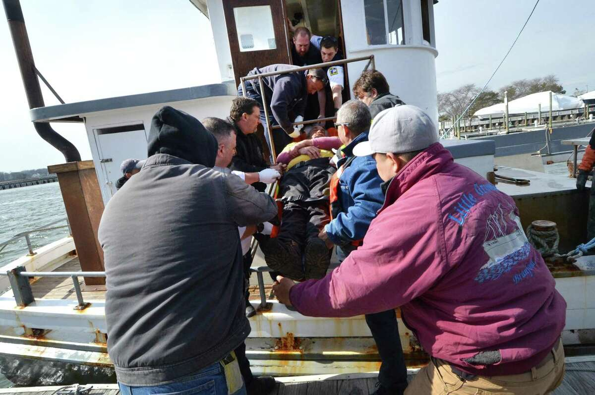Norwalk Fire Department Marine Unit 238, Norwalk police and Norwalk Hospital paramedics along with crew members help to lower a crew member from the Norm Bloom and Son/Copps Island Oysters boat Ringgold Brothers onto the dock at Cove Marina after recieving a 911 call for a medical emergency on Long Island sound on Monday.
