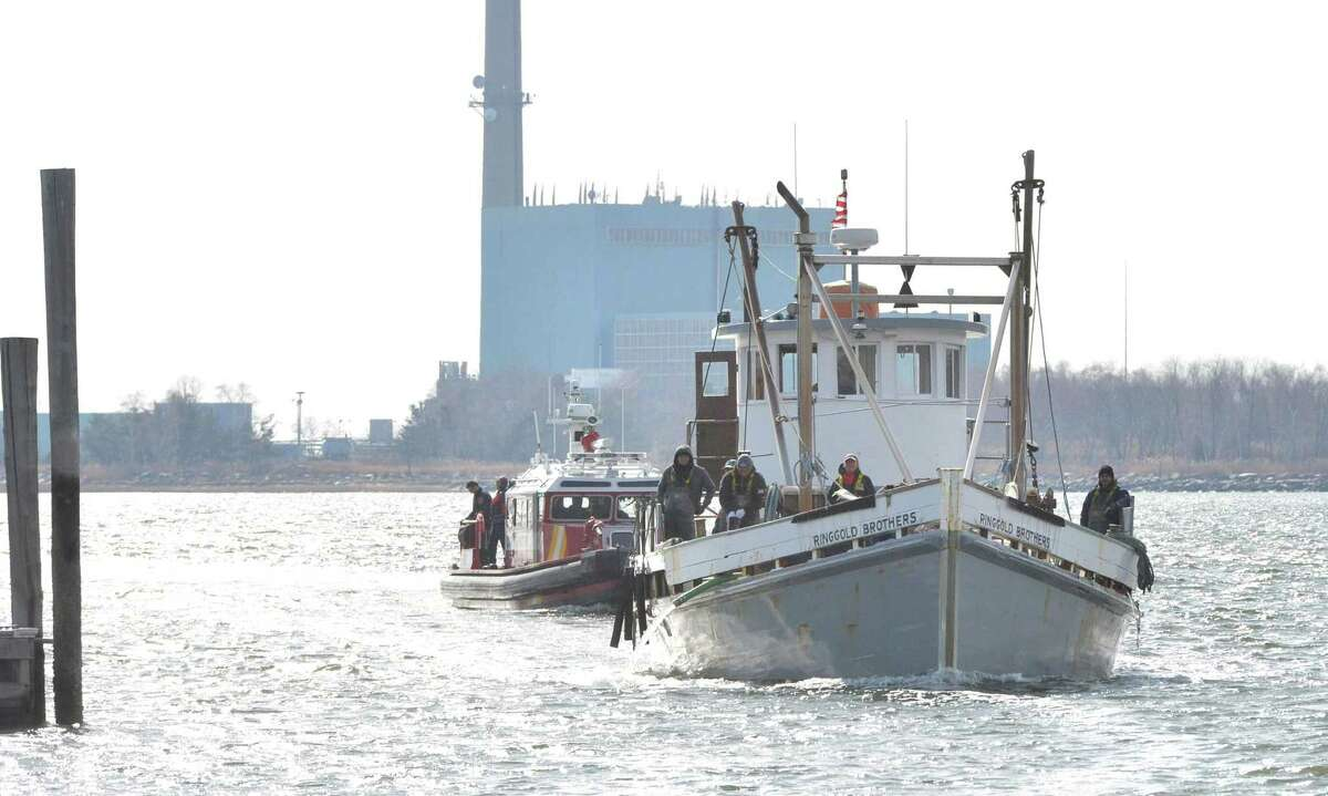 The oyster boat Ringgold Brothers makes its way into Cove Marina followed by the Norwalk Fire Department's Marine Unit 238 after calling for medical help on Long Island Sound for a crew member on Monday.