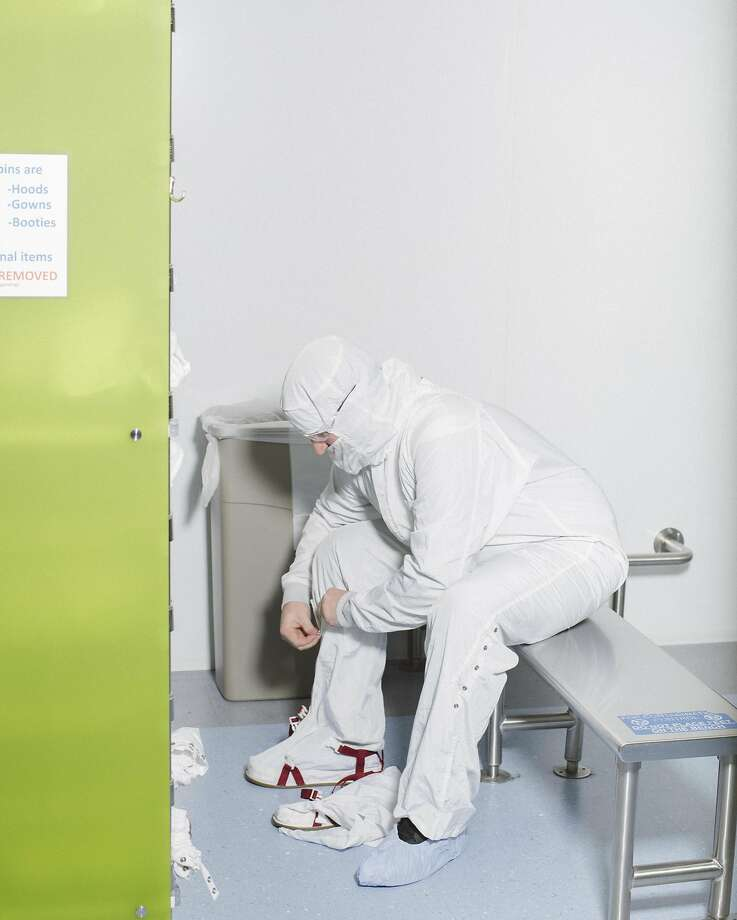 Adam Hendrickson demonstrates changing his clothes from the clean-room at the IM Flash plant, which was built in 1994 in Lehi, Utah. It is partly owned by Intel. Photo: JIM MCAULEY, NYT