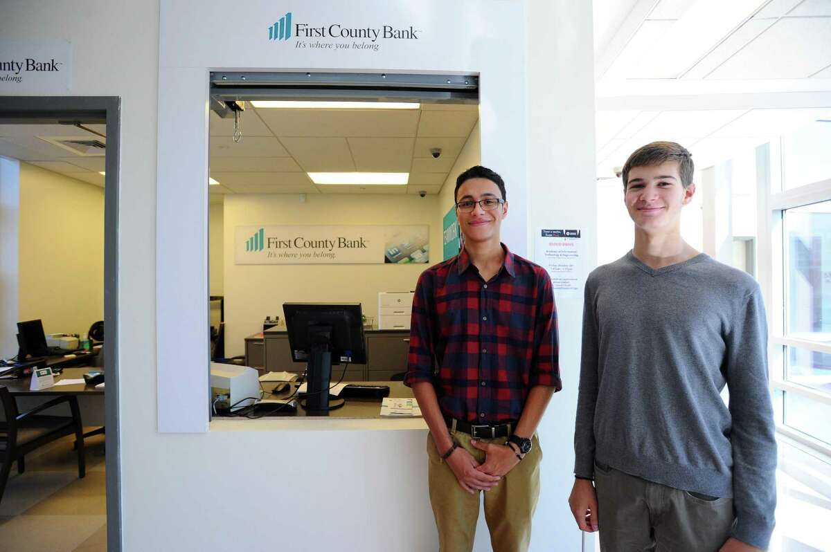 Academy of Information Technology and Engineering student interns Marco Lima, center, and Alex Graf pose outside First County Bank's limited-access branch at AITE. Opened in 2016, the branch represents one of First County's major financial-literacy initiatives.