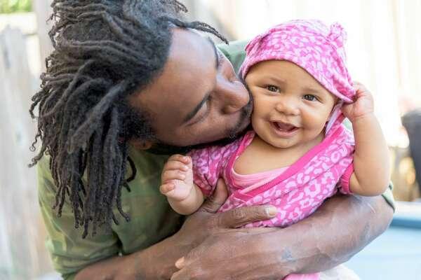 African american man posing posing holding his baby daughter   Baby stock image photo