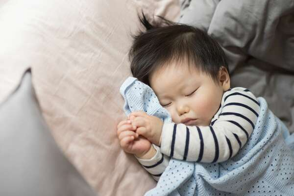 11 months old baby boy sleeping on bed Baby stock image photo