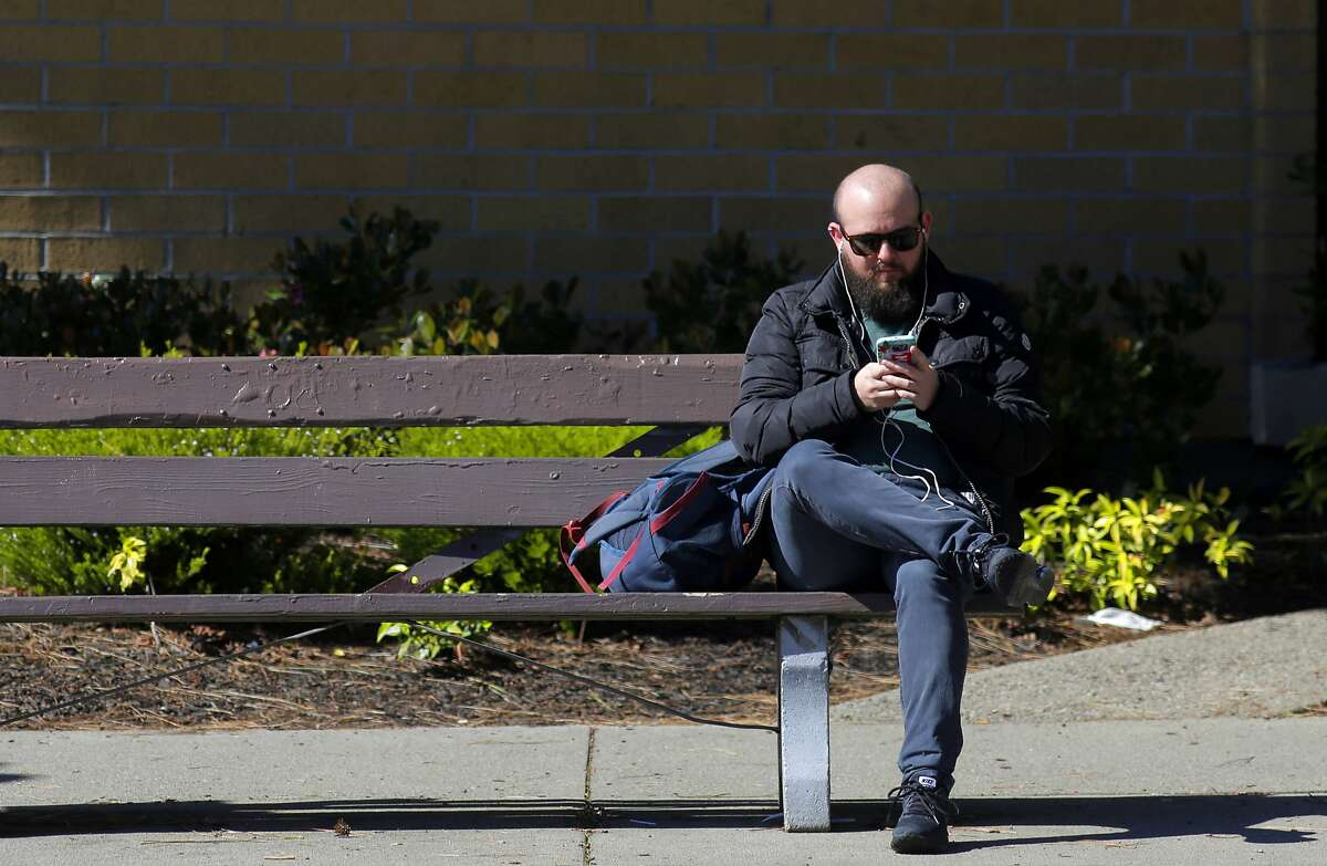 Nathan Gold of Berkeley said he uses ear buds for the most part when using his cell phone, seen as as he sits along Telegraph Ave. in Berkeley, Ca. on Monday February 27, 2017.