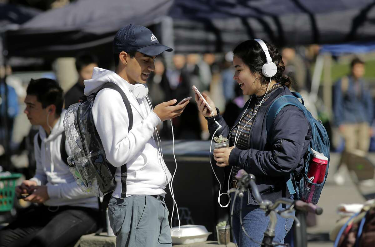 UC Berkeley students Kimberly Rodriguez and fellow student, (who declined to give his name) said they use headphones sometimes when making calls on their cell phones as seen on campus, in Berkeley, Ca. on Monday February 27, 2017.