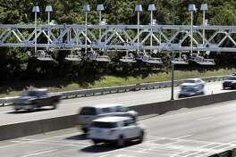 Cars pass under toll sensor gantries hanging over the Massachusetts Turnpike, Monday, Aug. 22, 2016, in Newton, Mass.