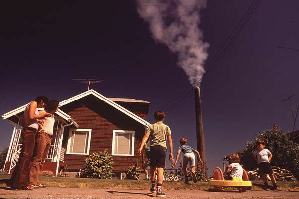 Original Caption:  Children Play in Yard of Ruston Home, While Tacoma Smelter Stack Showers Area with Arsenic and Lead Residue,   Date:  August, 1972.
