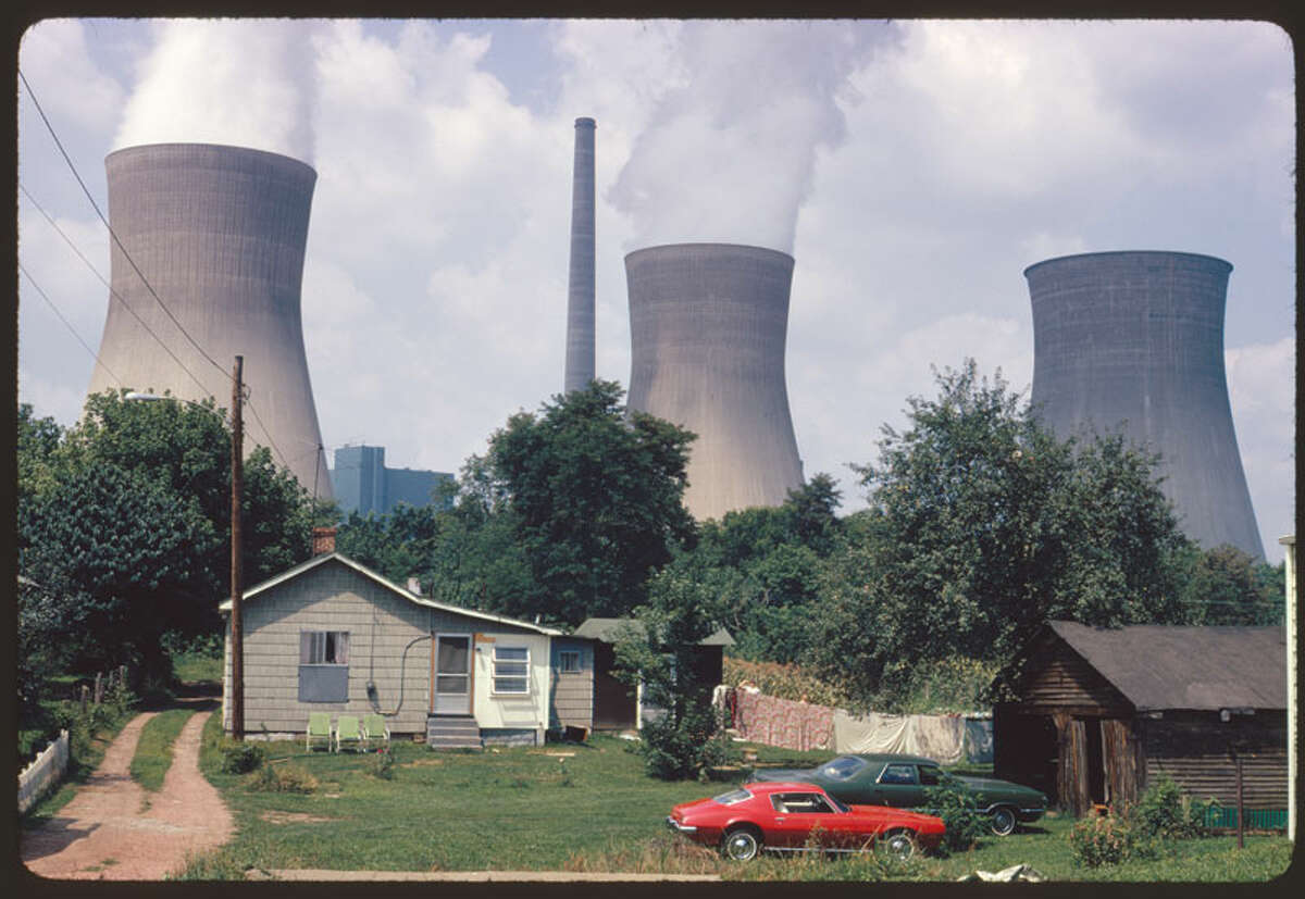 Original caption: Water cooling towers of the John Amos Power Plant loom over Poca, WV, home that is on the other side of the Kanawha River. Two of the towers emit great clouds of steam. Date: August, 1973.
