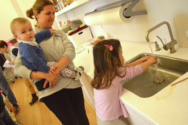 Clean-up time for Alina Leonova of Greenwich, daughter Veronica, 2, and Max, 15 months, at the Open Art Studio for Kids at Grace Farms, Saturday, Feb. 25, 2017, in New Canaan, Conn.