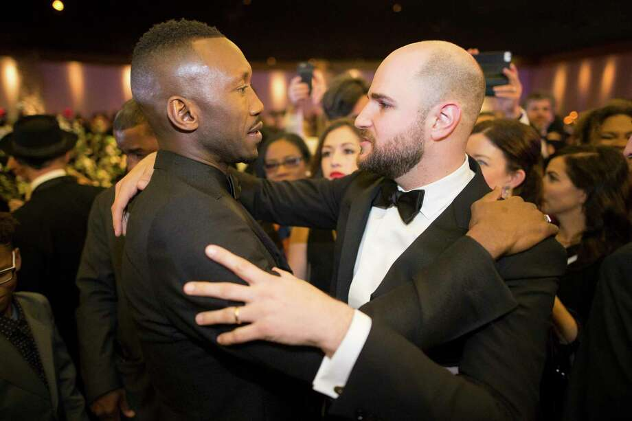 "Mahershala Ali, left, of ""Moonlight"" and Jordan Horowitz, the producer of ""La La Land,"" embrace at the Governors Ball following the 89th Academy Awards on Sunday. Photo: NOEL WEST, STR / NYTNS"