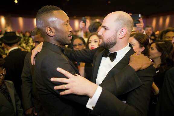 """Mahershala Ali, left, of """"Moonlight"""" and Jordan Horowitz, the producer of """"La La Land,"""" embrace at the Governors Ball following the 89th Academy Awards on Sunday."""