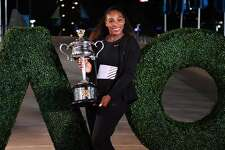 Serena Williams of the US poses with the championship trophy after her victory against Venus Williams of the US in the women's singles final on day 13 of the Australian Open tennis tournament in Melbourne on January 29, 2017. / AFP / SAEED KHAN