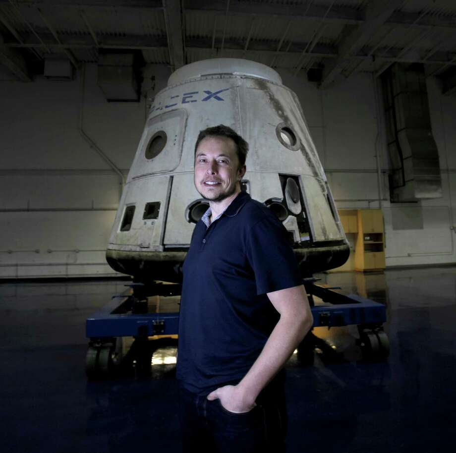 """SpaceX founder Elon Musk stands in front of the SpaceX Dragon capsule at Space Exploration Technologies Corp. Musk wouldn't identify the pair of private citizens who will go fly on next year's moon mission or the price tag. They've already paid a """"significant"""" deposit, he noted. Photo: Brian Van Der Brug /Los Angeles Times / Los Angeles Times"""