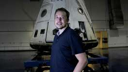 "SpaceX founder Elon Musk stands in front of the SpaceX Dragon capsule at Space Exploration Technologies Corp. Musk wouldn't identify the pair of private citizens who will go fly on next year's moon mission or the price tag. They've already paid a ""significant"" deposit, he noted."