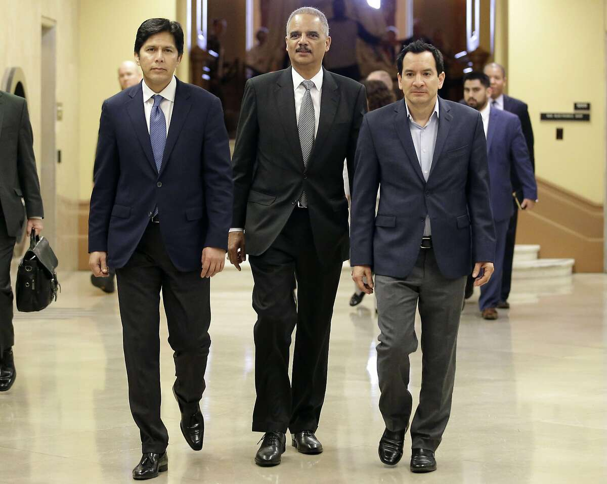 Former U.S. Attorney General Eric Holder, center, flanked by California Senate President Pro Tem Kevin de Leon, D-Los Angeles, left, and Assembly Speaker Anthony Rendon, D-Paramount, walks to a meeting with Calif., Gov. Jerry Brown, Tuesday, Feb. 7, 2017, in Sacramento, Calif. Holder has been hired by Democratic leaders of California's legislature to represent them in legal issues against President Trump and his administration. (AP Photo/Rich Pedroncelli)