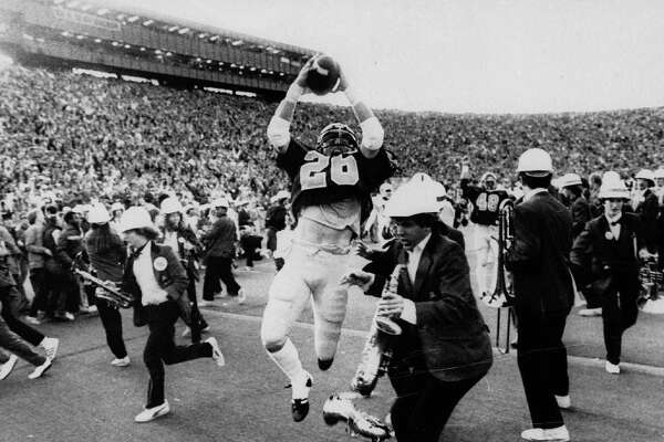 ** FILE ** California's Kevin Moen (26) leaps with the ball in the air after scoring Cal's winning touchdown while the Stanford band runs to get out of his way in Berkeley, Calif., in this Nov. 25, 1982 photo. When the Big Game rolls around each fall, Kevin Moen and Gary Tyrrell can't help being reminded about their roles in the wackiest four seconds in college football history. In 1982, Moen scored for California on the game-ending, five-lateral kickoff return known simply as The Play _ and Tyrrell was the Stanford band's trombone player who got leveled by Moen in the end zone. (AP Photo/Oakland Tribune/Robert Stinnett)