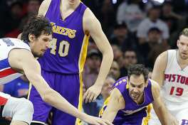 Detroit Pistons center Boban Marjanovic, left, and Los Angeles Lakers guard Jose Calderon reach for the loose ball during the second half of an NBA basketball game, Wednesday, Feb. 8, 2017, in Auburn Hills, Mich. (AP Photo/Carlos Osorio)