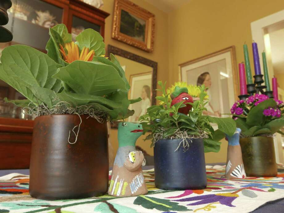 Water glasses in bright colors purchased at a garage sale hold gerbera daisies, kalanchoe and goldfish plants. Photo: Billy Calzada /San Antonio Express-News / San Antonio Express-News