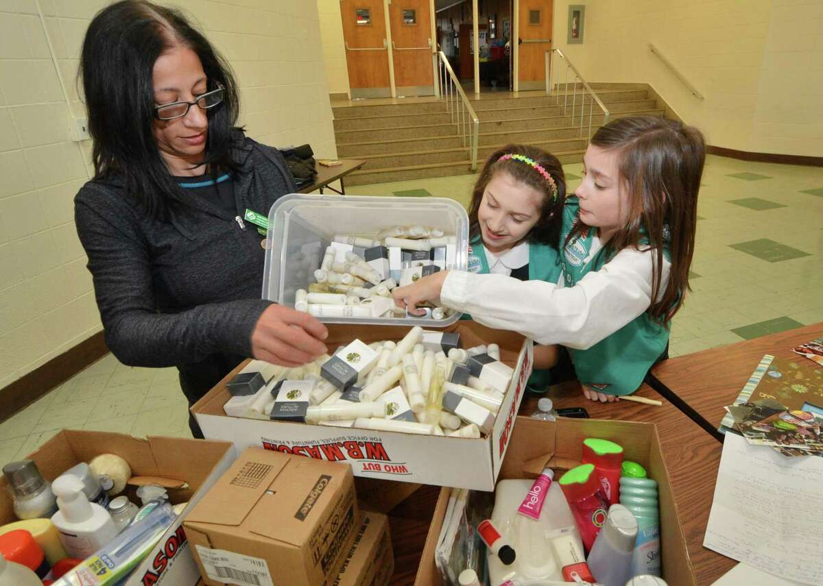 Sorting shampoo for distribution, at All Saints Catholic School, Troop leader Susan Horn along with scouts Grace Baez and Katie Horn with the Girl Scouts from Troop 50302 who are pursuing their Bronze Award and have created a program to reduce waste in the hospitality industry. They are collecting unused toiletries such as soap and shampoo and pass them on to people that need them through the group Kids in Crisis and the Open Door Shelter. on Monday February 27, 2017 in Norwalk conn.