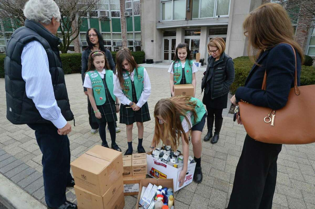 At All Saints Catholic School, the Girl Scouts from Troop 50302 who just earned their Bronze Award for creating a program to reduce waste in the hospitality industry and help the less fotunate carry the donations out. They collected and delivered unused toiletries such as soap and shampoo and pass them on to people that need them through the group Kids in Crisis' Kristen Tomasiewicz and Andrea Arnold and Corky Stewart and Erin McDonough with the Open Door Shelter. on Monday February 27, 2017 in Norwalk conn.