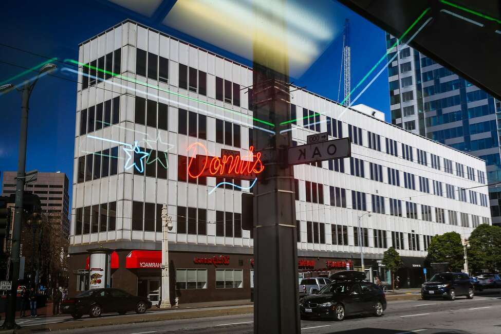 The 30 Van Ness Avenue city office building is seen in the reflection of a coffee shop in San Francisco. The Board of Supervisors has agreed to sell it for $70 million.