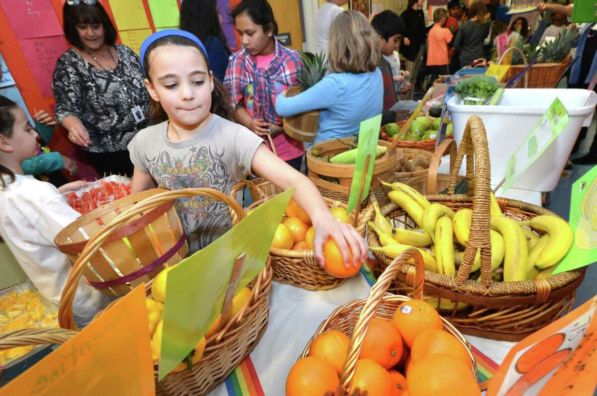 Maren Gilchrist, 5th grader at Columbus Magnet School, fills her basket with fresh produce like watermelon, kiwi, grapefruit and pears as she reaches for an orange and heads to the checkout as first graders run a real produce market for the day at the school on Monday February 27, 2017 in Norwalk Conn.