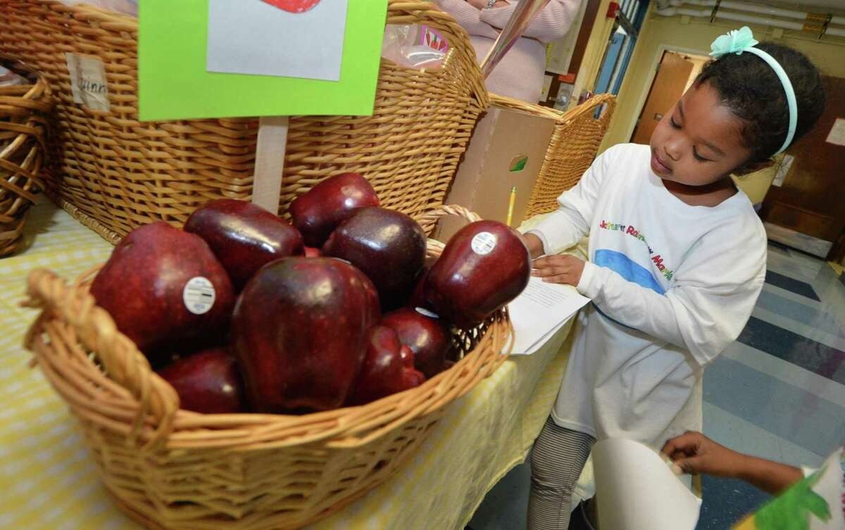 1st grader Alyna Thomas works on her shopping list before she fills her basket at Columbus Magnet School, as first graders run a real produce market for the day at the school on Monday February 27, 2017 in Norwalk Conn.